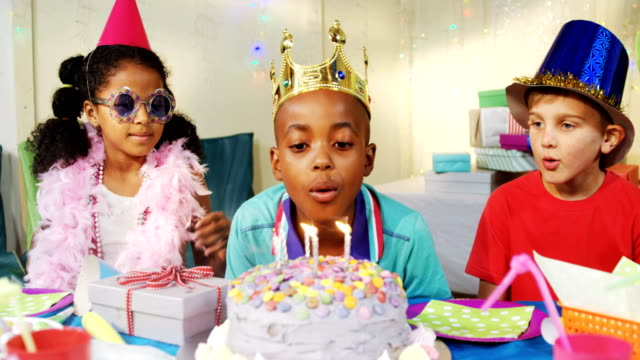 Boy blowing candles on cake during birthday 4k video