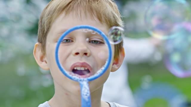 Boy Blowing Soap Bubbles at Camera video
