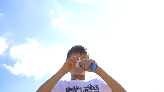 Boy Blowing Soap Bubbles Outdoors On A Sky Background, Slow Motion video