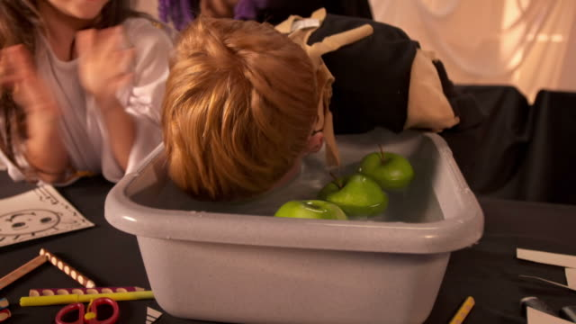 HD: Boy Bobbing For Apple At Halloween Party