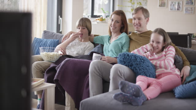 vídeos de stock e filmes b-roll de boy bringing popcorn to family sitting on the sofa - sala