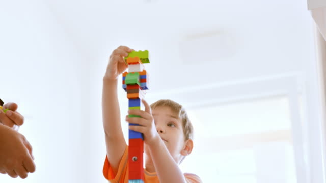 vídeos de stock e filmes b-roll de boy building a high plastic brick tower with father - bloco