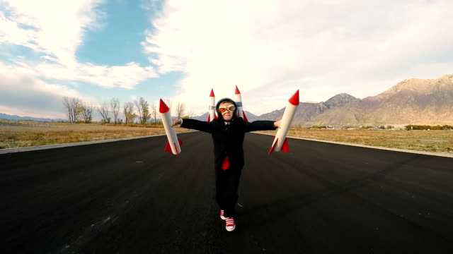 Boy Businessman Holding Rockets Imagines Flying video