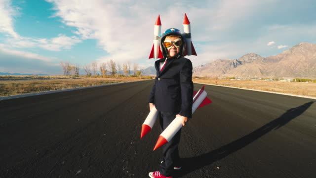 Boy Businessman Holding Rockets Imagines Flying
