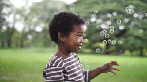 vídeos y material grabado en eventos de stock de niño atrapa burbujas de jabón en parque público - edad humana