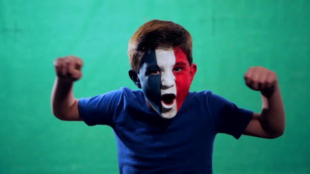 vídeos de stock e filmes b-roll de boy celebrates france victory - soccer supporter portrait