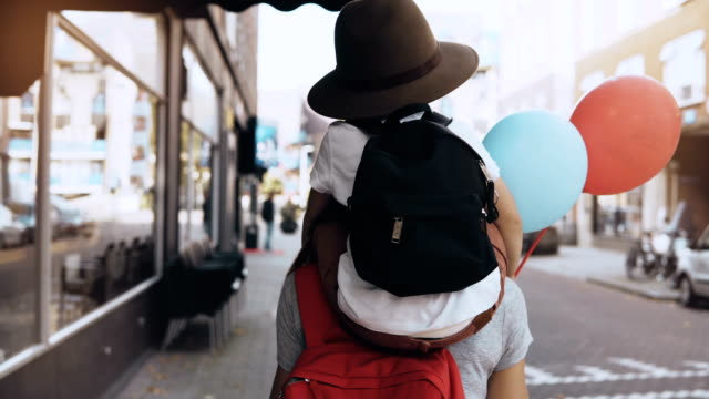 boy child on mom's shoulders, two air balloons. mother and son in hat with backpack walk together along the street. 4k - viaggiare zaino in spalla video stock e b–roll