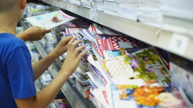Boy choosing buying stationery in store preparing for first day in school.