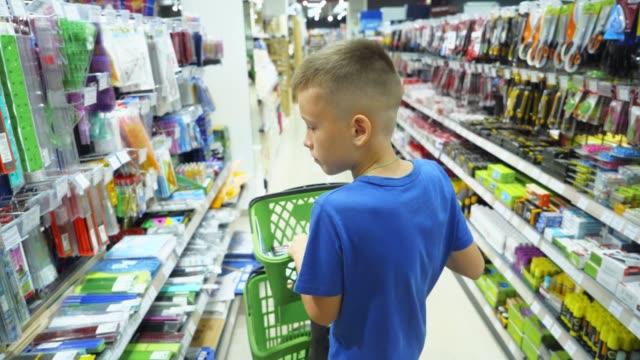 vidéos et rushes de garçon, choisir l'achat d'articles de papeterie en magasin prépare pour le premier jour à l'école. - fournitures scolaires