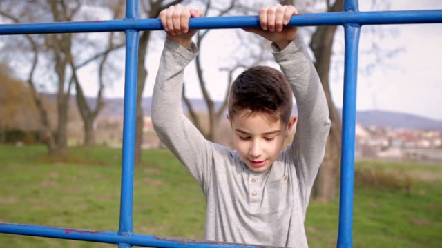 Boy climb on the equipment for playing video