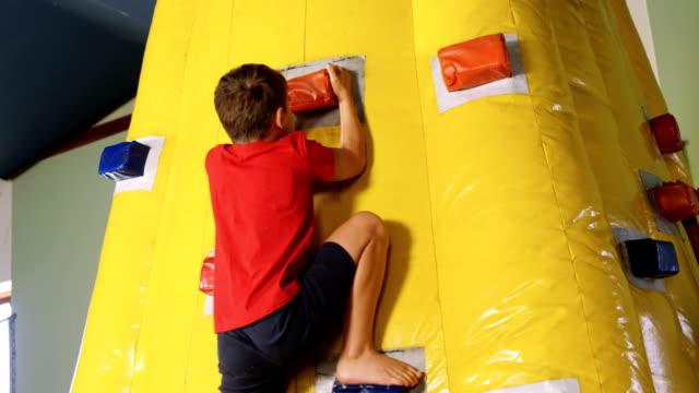 Boy climbing bouncy castle 4k video