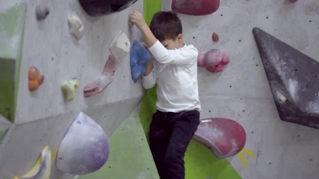 vidéos et rushes de escalade falaise couverte garçon - lieu sportif