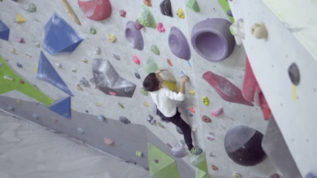 junge indoor rock kletterwand - bouldering stock-videos und b-roll-filmmaterial