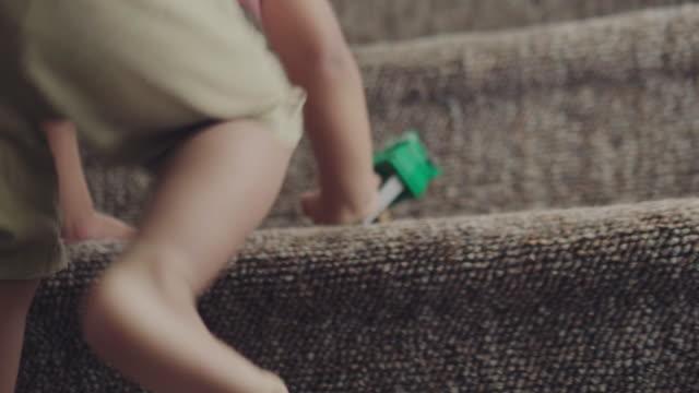 boy climbing steps - moquette video stock e b–roll