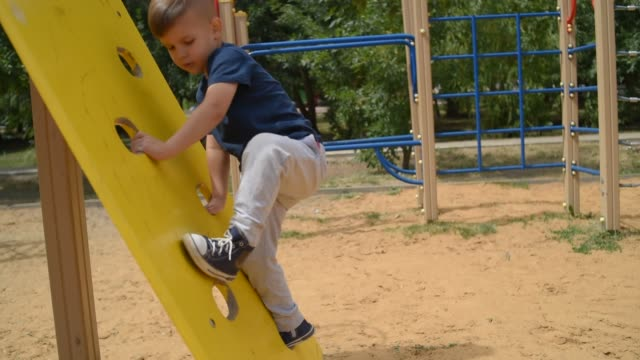 boy climbs up the climbing wall on the playground in summer