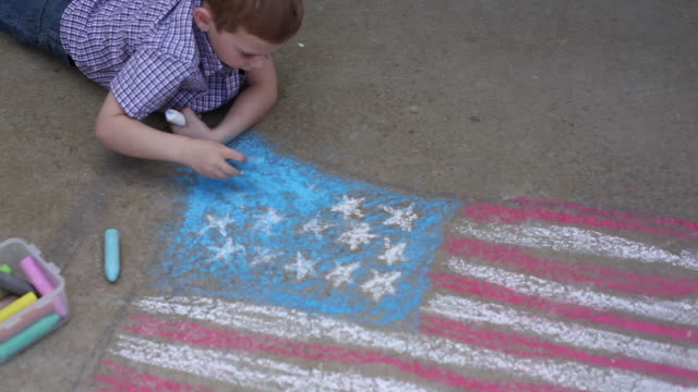 Boy coloring American flag with chalk video