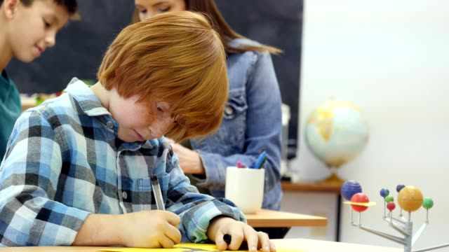Boy concentrates while working on solar system project video