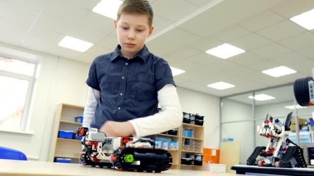 мальчик управляет современным роботом. 4k. - манипулятор робота производственное оборудование стоковые видео и кадры b-roll