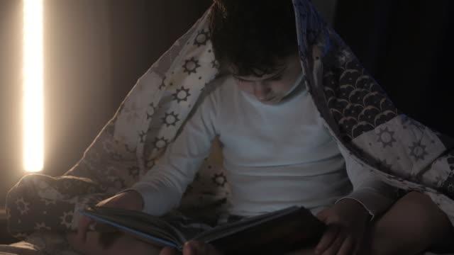 pojke täckt filt. kväll, läsbok i sovrummet på sängen. - digital reading child bildbanksvideor och videomaterial från bakom kulisserna