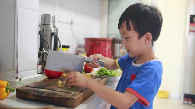 vídeos de stock e filmes b-roll de boy cutting brocoli for cooking at domestic kitchen - utensílio