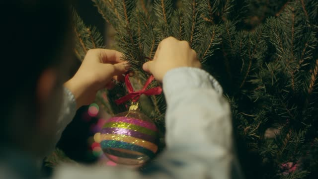 vídeos de stock e filmes b-roll de boy decorating christmas tree at home - arvore de natal