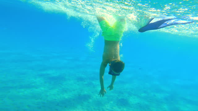 Boy diving to the seabed