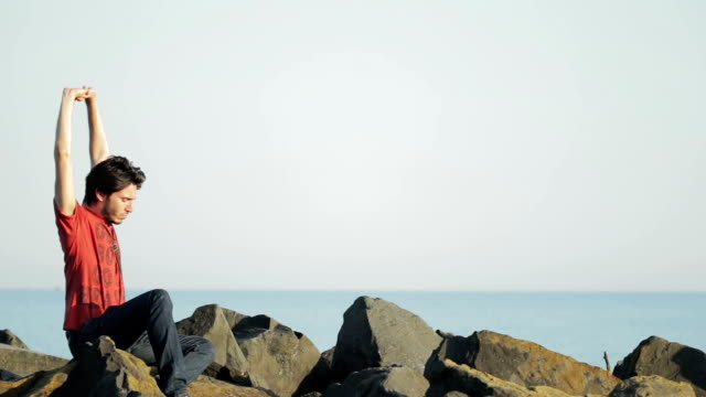 Boy does stretching in front of the sea - relax on the rock in the sea video