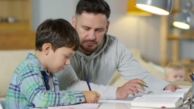 pojken gör läxor med pappa - parent talking to child bildbanksvideor och videomaterial från bakom kulisserna
