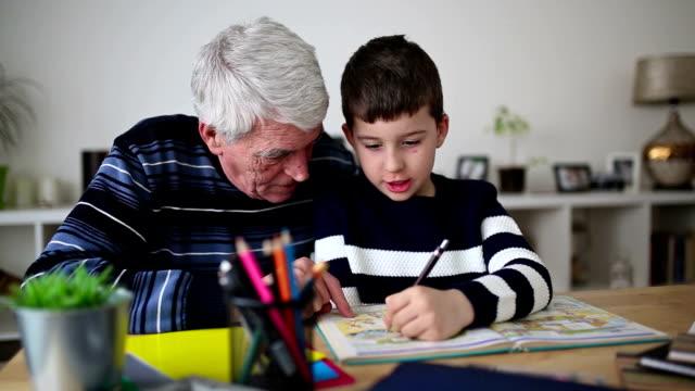 vídeos y material grabado en eventos de stock de chico haciendo la tarea con su abuelo - abuelos