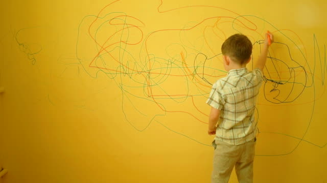 boy drawing on the yellow wall at home - muro video stock e b–roll