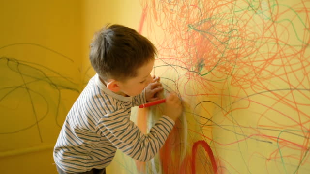 Boy drawing on the yellow wall at home