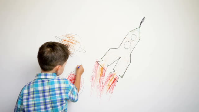 boy drawing the rocket on white wall - kids drawing стоковые видео и кадры b-roll