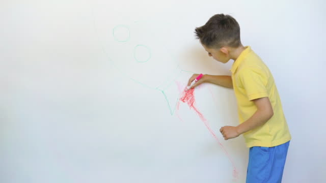 Boy drawing the rocket on white wall