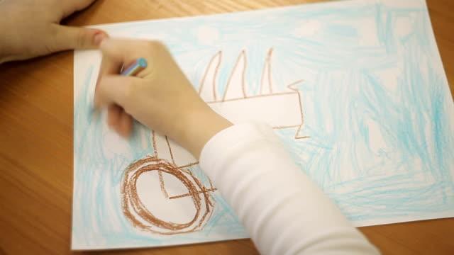 少年は、紙に鉛筆で車の車輪を描画します ビデオ