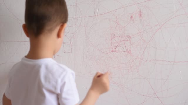 boy draws on the wall with colored chalk. the child is engaged in creativity at home - matita colorata video stock e b–roll