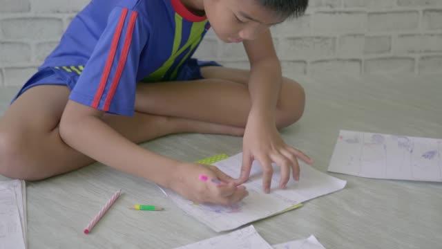 pojke ritar blyerts på ett pappersark. - linjerat papper bakgrund bildbanksvideor och videomaterial från bakom kulisserna