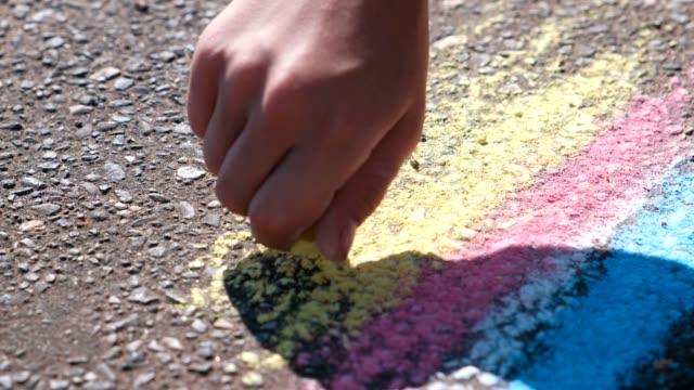 vídeos de stock, filmes e b-roll de menino desenha com giz azul no asfalto. mãos de close-up. - calçada