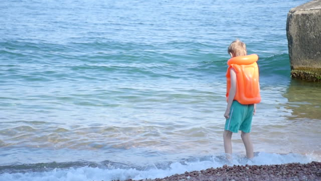 boy dressed in inflatable lifejacket on beach of the sea video
