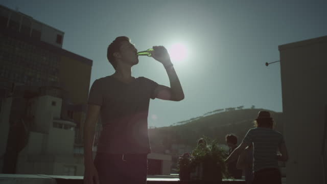 Boy drinking beer on rooftop video