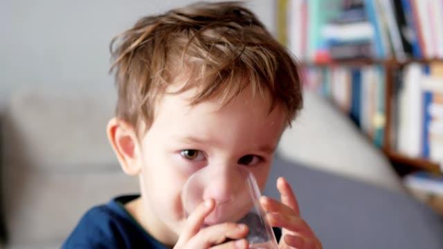 stockvideo's en b-roll-footage met jongen drinkwater uit glas - water drinken