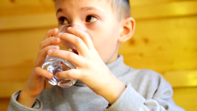 Boy drinking water Young boy of 5 years drinking water in small sips from glass. Bright wooden background. Close up. one boy only stock videos & royalty-free footage