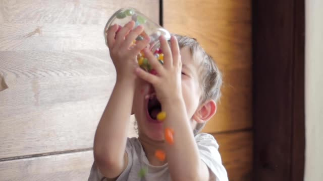 boy eating candies falling from jar - dolci video stock e b–roll