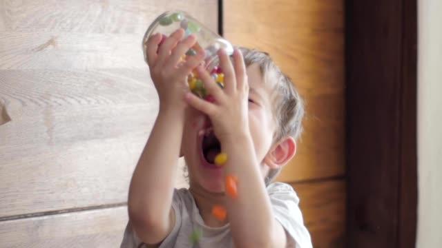 vídeos y material grabado en eventos de stock de niño comiendo caramelos caer de la jarra - postre