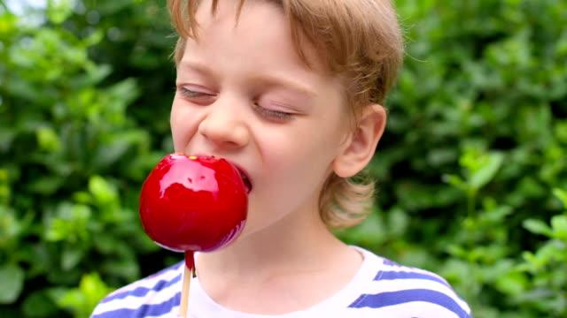 boy eating caramelized apples video