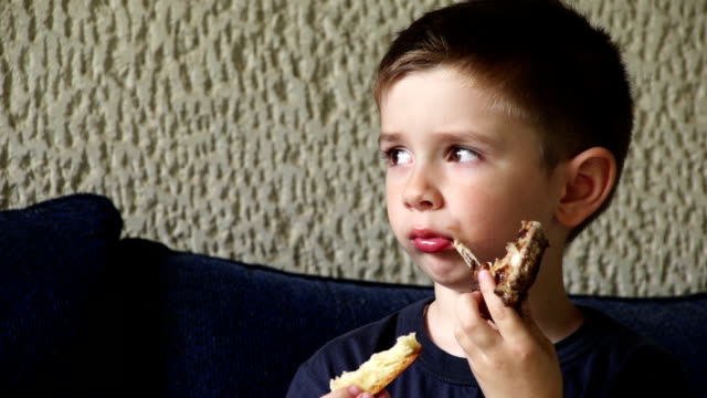 Boy eating chicken wings and bread video