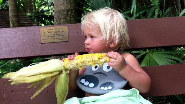 Boy eating corn on a bench