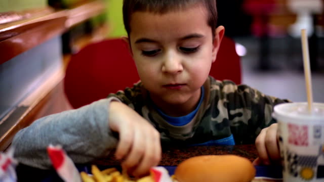 Boy eating fast food and enjoyoing it video