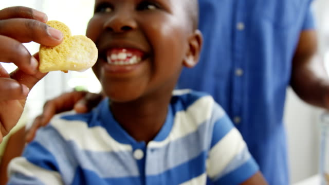 Boy eating heart shape cookie Boy eating heart shape cookie at home cookie stock videos & royalty-free footage