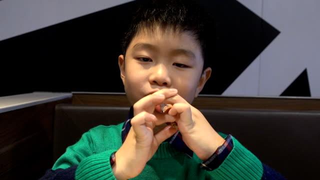 실내에 닭 뼈를 먹는 소년 - burger and chicken 스톡 비디오 및 b-롤 화면