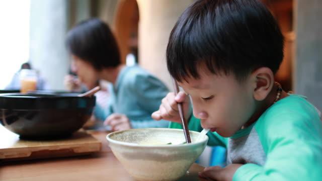 Boy eats rice noodles with chopsticks